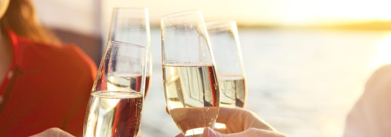 Happy friends with glasses of champagne on yacht. Vacation, travel, sea and friendship concept. Closeup.